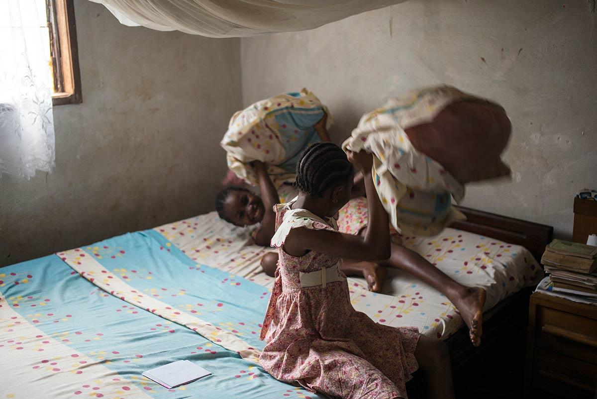 Maeva Cahey Florine. Operada de una malformación genética , juega con su hermana en su habitación. Younde, Camerún.
