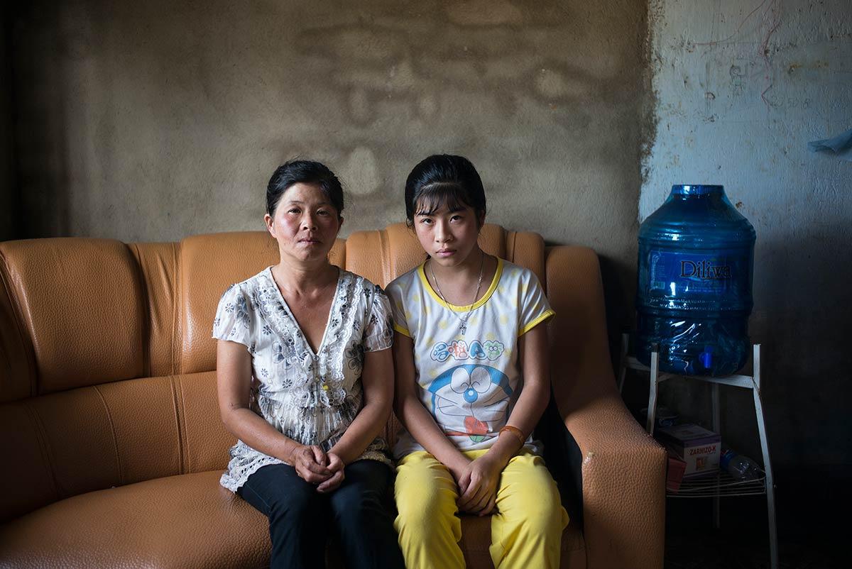 Cao Thi Khanhuyen. Operada de un problema cardíaco, posa junto a su madre en el comedor de su casa en Dalat, Vietnam.