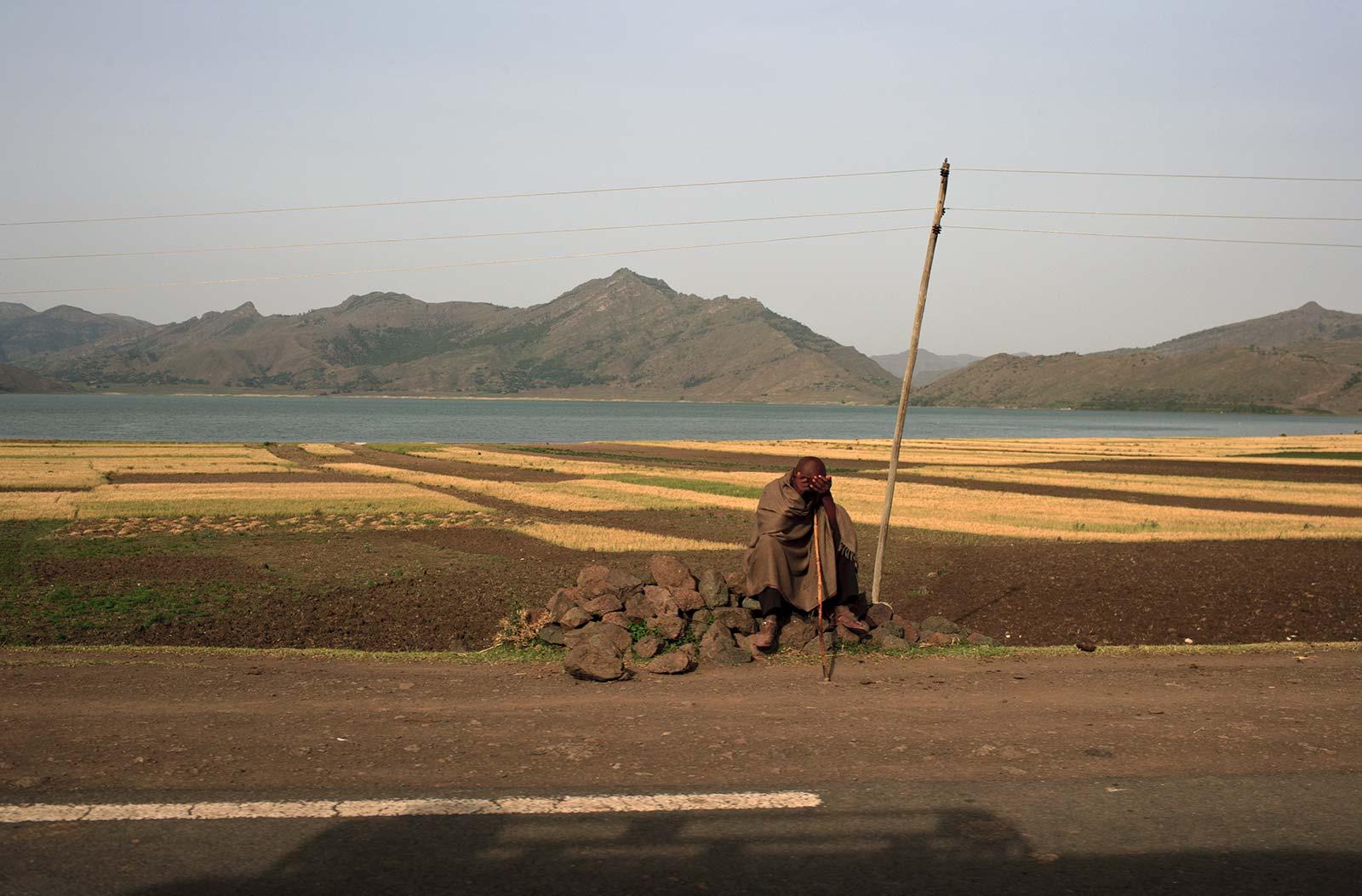 ROAD TO THE NORTH Hombre sentado en la carretera a Mekelle. Lago Awasa.